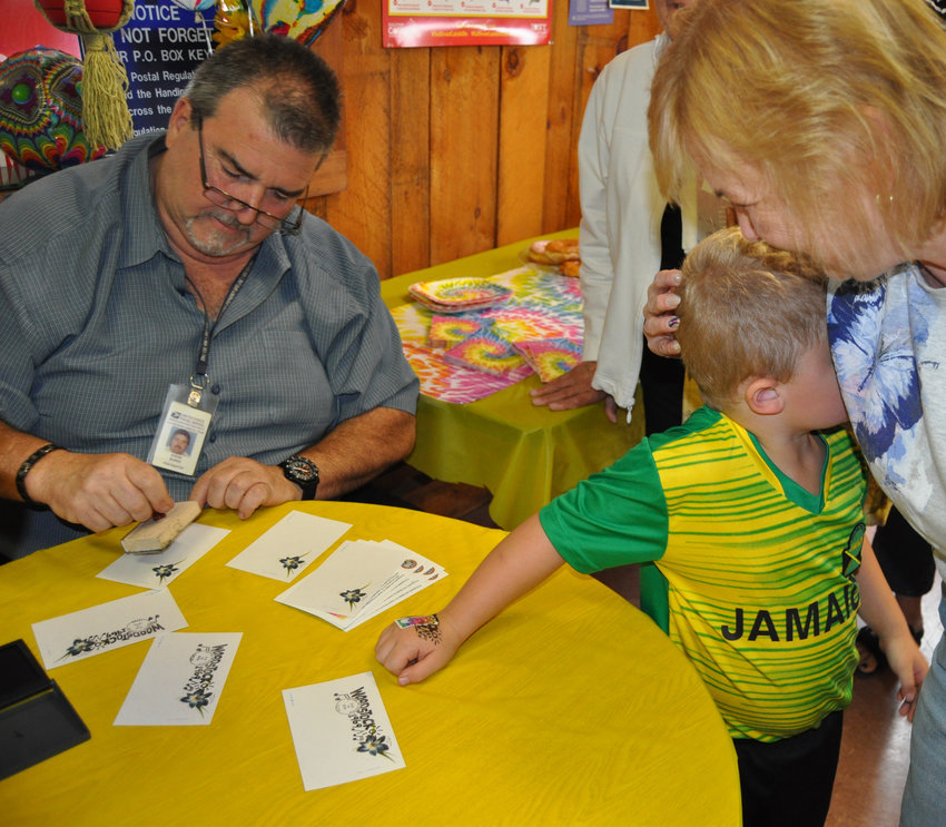 "Four year-old Charlie was the ""first ever"" to get a Woodstock anniversary stamp cancelled right on his hand!"