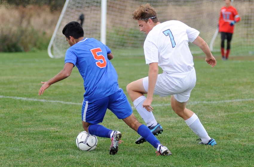 Perfect form in unison. Seward's Nick Campana faces off against Sullivan West's Ryan Mace as they battle for possession.