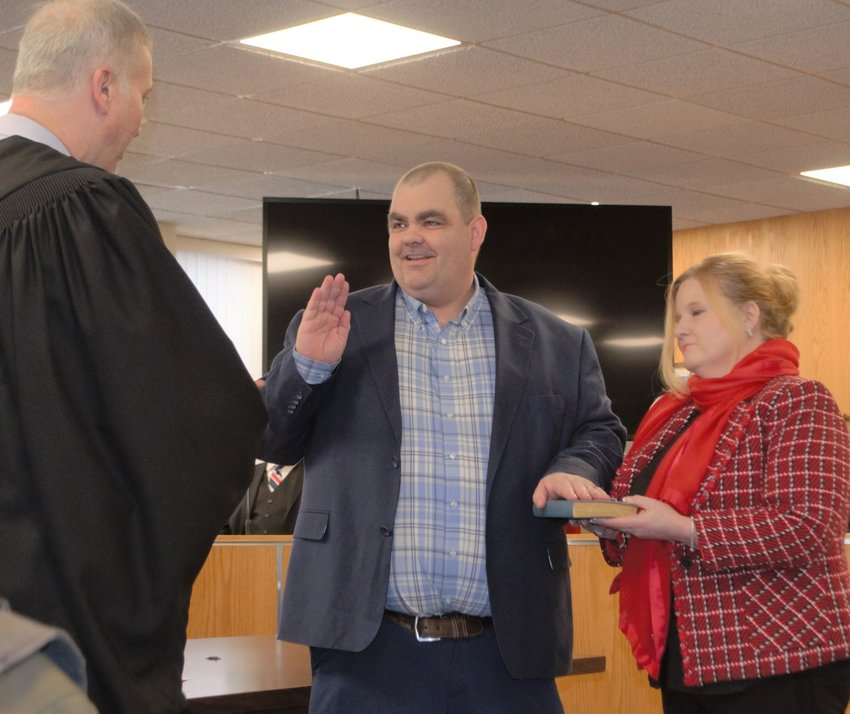 With his wife Cathleen Crumley-Doherty holding the Bible, Rob Doherty is sworn in as the new chairman of the Sullivan County Legislature.