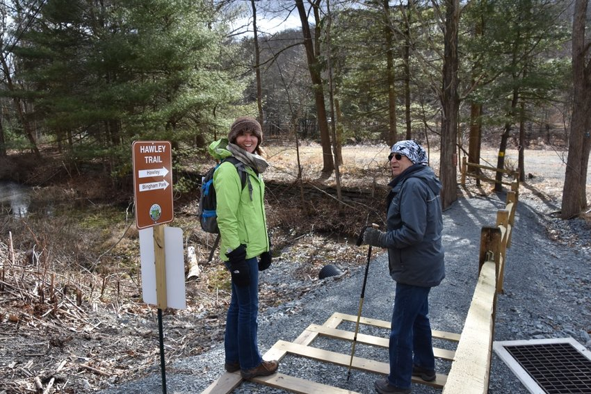 Delaware Highlands Conservancy's Amanda Subjin and Hawley, PA business owner Grant Genzlinger discuss the history of the recently completed Hawley Trail in preparation for a guided walk on Saturday, April 18. Visit www.bit.ly/hawleyearthweek to learn more.