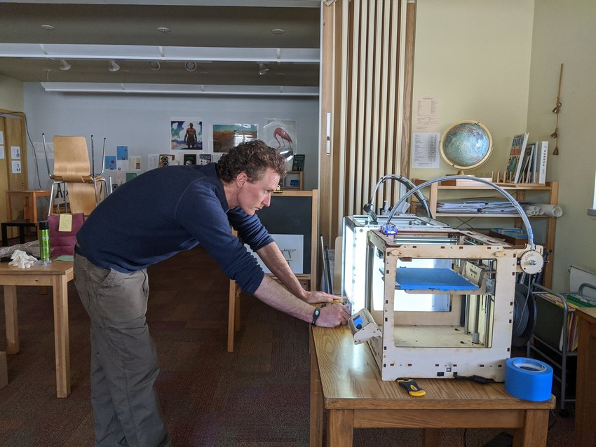 Homestead School Assistant Headmaster Jack Comstock checks the 3D printer that is being used to produce face masks and protective shields.