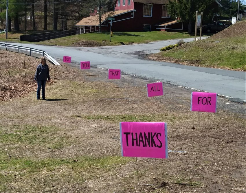 """A passing thank-you: Julie Dreher Setren stands by signs she and her husband Lou made to let the staff of Care Center at Sunset Lake know """"how much they're appreciated by all for going above and beyond during this critical time."""""""