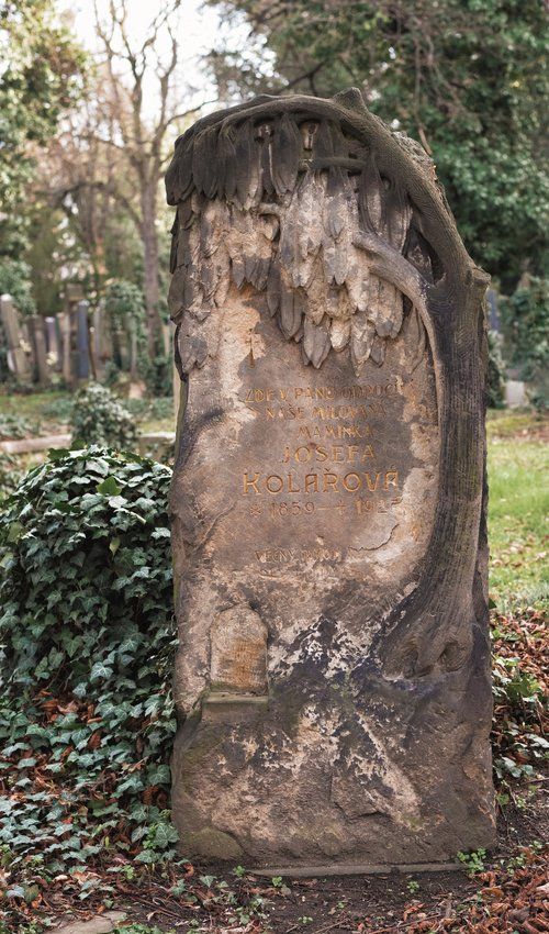 A headstone with a weeping willow-type tree.