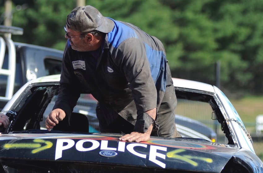 "Exit lane. Michael Wiener, owner of Russell's Garage in Loch Sheldrake, NY climbs out the rear window of his Ford Crown Victoria racecar, ""Police."""