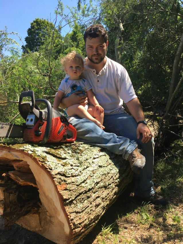 My son and I sit atop the freshly felled Hemlock in our yard.