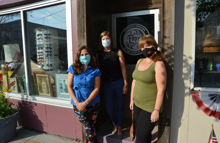 Alison Hoffmann, left, Sarah Clauss and Jill Carletti stand in front of the historic Murray building on Main Avenue in Hawley, now home to their creation: the Hawley Hub.