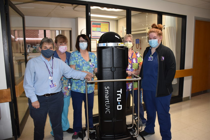 Environmental Services staff Michelle Miller, left, Mary Moser, Patricia Reahm, Gail Reynolds and Molly Nagle with Tru-D Smart UVC robot in the Intensive Care Unit.