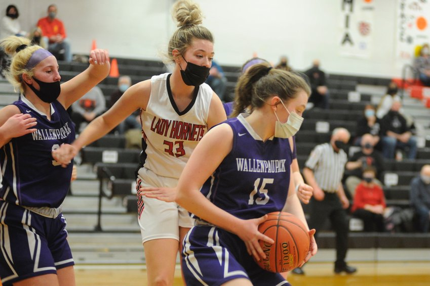 Decision on the boards. Honesdale junior bucketeer Chloe Lyle closes in on Wallenpaupack's Megan Desmet who posted a game-high 26 points, including going 17/21 at the free-throw line.