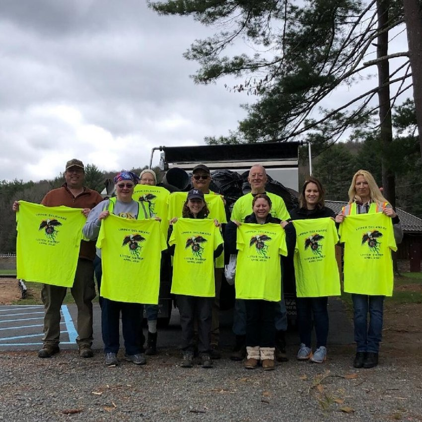 "Team Lackawaxen proudly displays the Upper Delaware Litter Sweep T-shirts they earned while collecting 1,300 pounds of roadside trash during a four-hour pick-up along three miles of Masthope Plank Road in Lackawaxen Township, PA on the first day of the April 17-25 event coordinated by the Upper Delaware Council. The intrepid team included Jeff ""JT"" Thompson, left, Ellen O'connor, Eileen Ahearn, Brenna O'connor, Jeffrey Shook, Dennis Ahearn, Jackie Decatur, Heather Clark, Lynn Mills, and behind the camera, Eric Thompson."