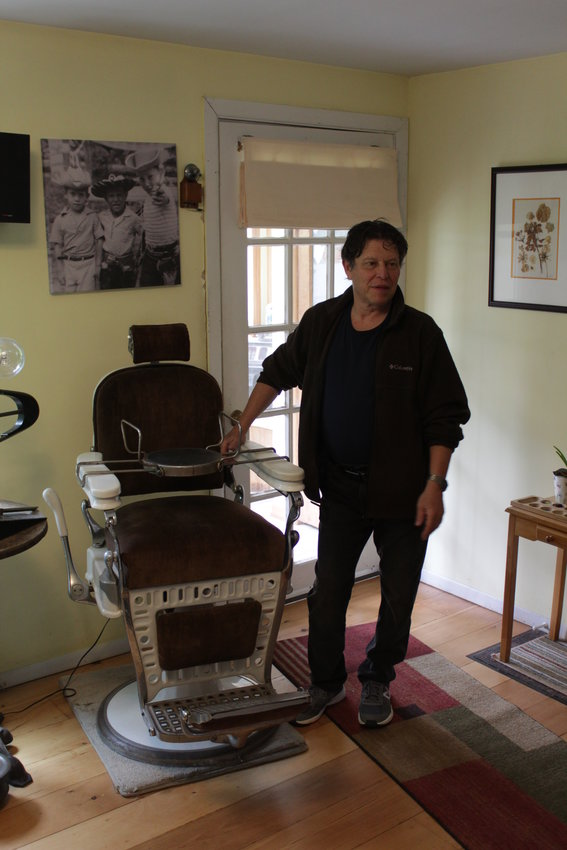 Allen Frishman shows off the barber's chair in which he had his early haircuts.