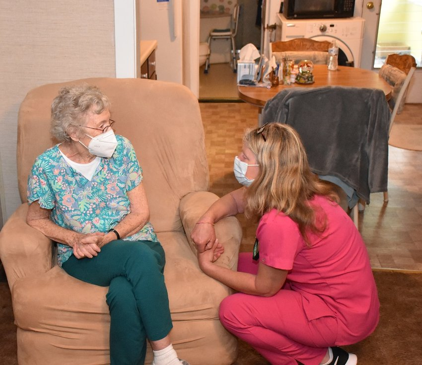 Helen Klinger, left, chats with RN Sue Flynn before receiving her COVID-19 vaccine at her Woodbourne home.