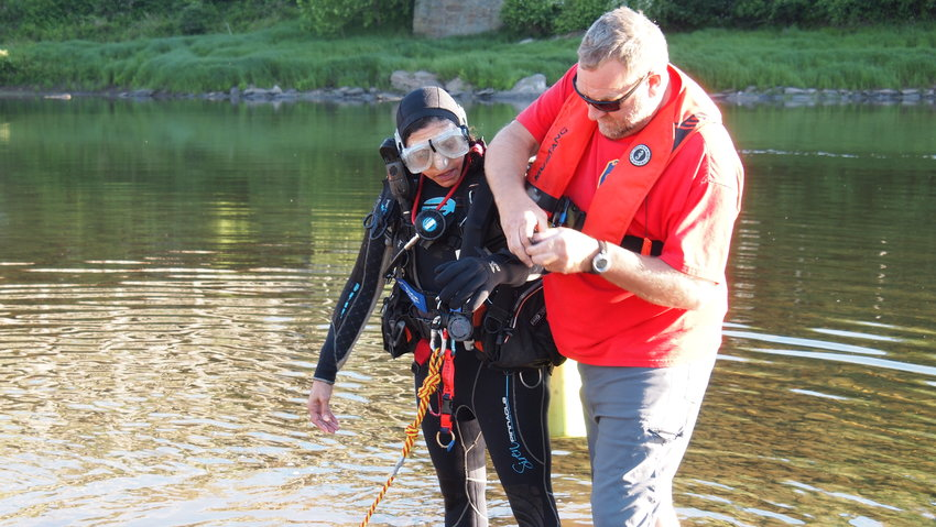 Sharon Doyle, left, a member of the Neversink Fire Department and president of the Sullivan County Dive Team, gets assistance from Joe Ratner, the dive team captain and a member of the Youngsville Fire Department.  The team was at Skinner's Falls in a drill hosted by the Cochecton Ambulance Corp. on June 16.