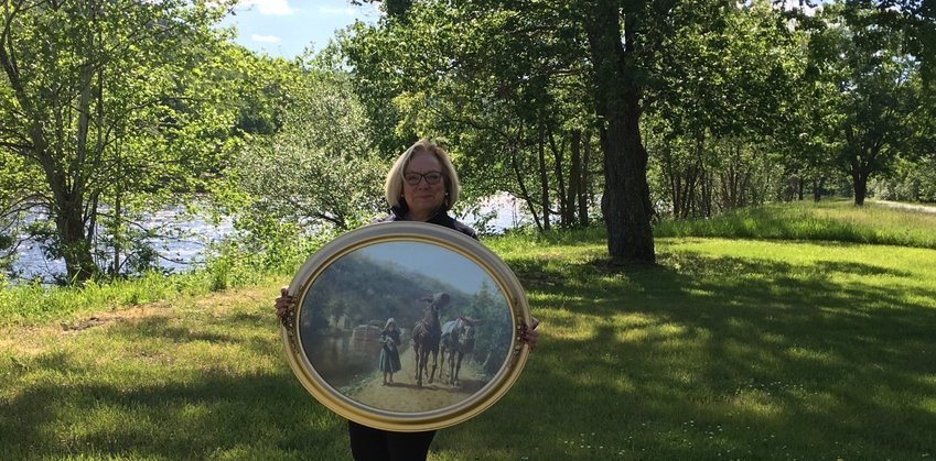 """Historian Debra Conway holds a print of E.L. Henry's 1891 painting, """"On the Towpath,"""" which inspired her to propose a hiking trail on a former D&H Canal towpath, which is in the background to the right."""