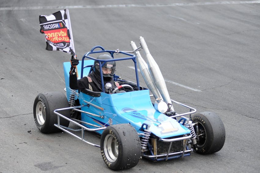 Checkered flag time. Tyler Wagner, the winner of the vintage division, takes a victory lap at the speedway.