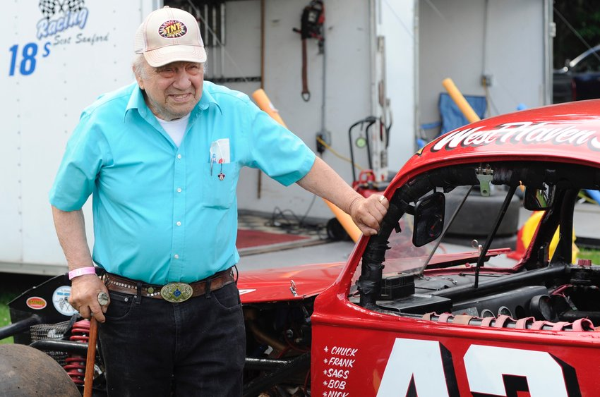 """Reflections of past glories. Billy """"Wild"""" Bill Greco poses next to #43 at Bethel Speedway during Danbury Racearena Night."""
