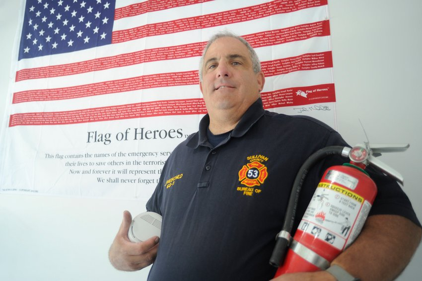 """John Hauschild, Sullivan County fire coordinator and Emergency Services Training Center coordinator, proudly stands in front of the center's """"Flag of Heroes,"""" which lists the names of the emergency services personnel who gave their lives to save others on September 11, 2001...He is pictured holding a smoke detector and a fire extinguisher, two key elements of fire prevention...""""We will always remember and never forget them... the sacrifices that were made by all,"""" said Hauschild of the roster of heroes."""