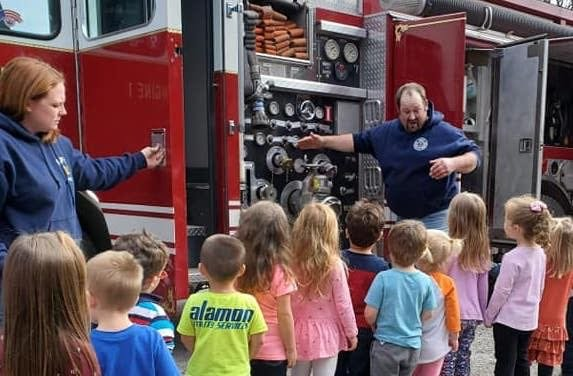 Fire company vice-president and line officer/firefighter Russell Yerkes shows a group of youngsters where everything is located in a modern-day fire apparatus, during a 2020 Fire Prevention Week demonstration at the Damascus School.