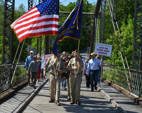 Members of the Tusten, Highland Lumberland VFW Post #6427 lead a procession of veterans and activists on the Pond Eddy Bridge, which is also named All Veterans Memorial Bridge, to drop a wreath into the water on Armed Forces Day, and to call for the preservation of the historic structure.