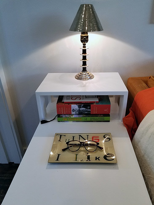 The nightstand and its collection of reading material