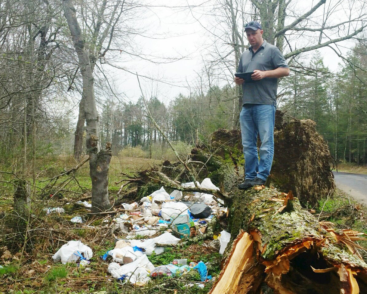 Pike Mathew Gayton of Fusco Engineering documents garbage that was dumped on Barton Road in Liberty.