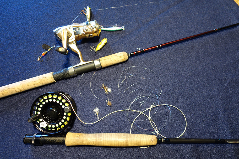 A spinning rod, reel, line and lures is shown at top; a fly-fishing rod, reel, line and flies at bottom.