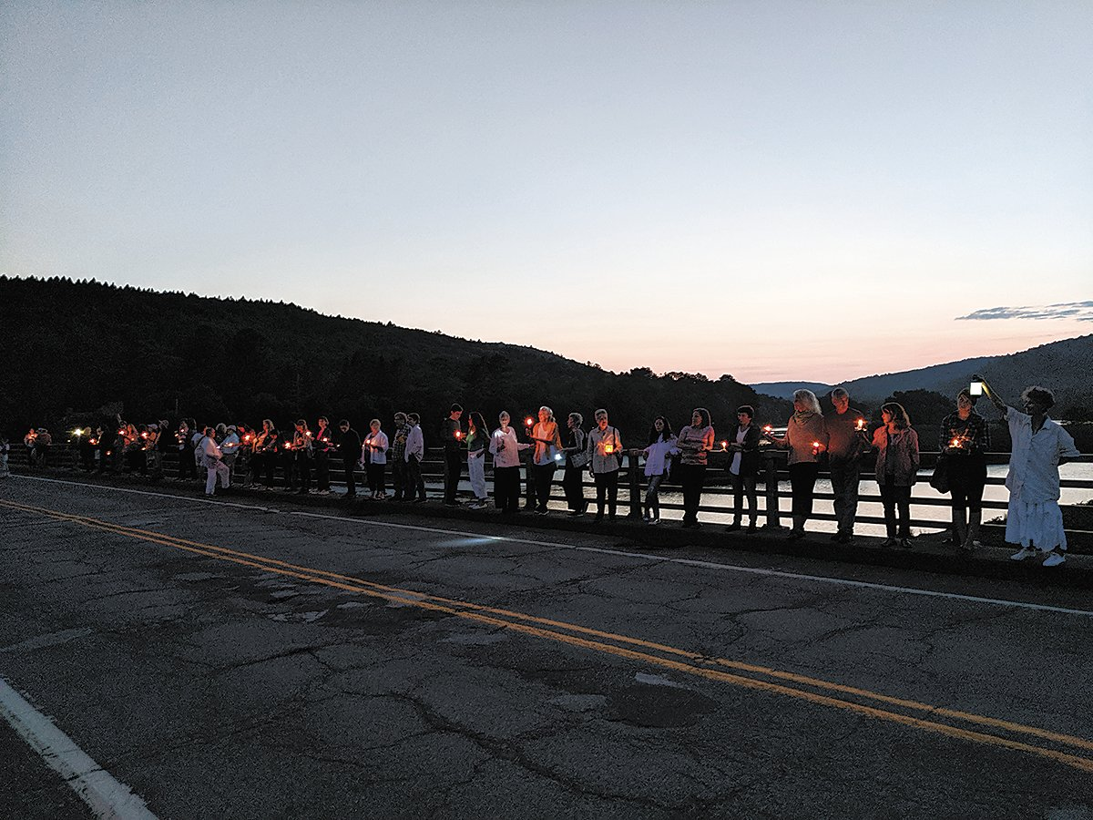 A group gathered on the Callicoon Bridge for a vigil in support of migrants in detention centers at the border.