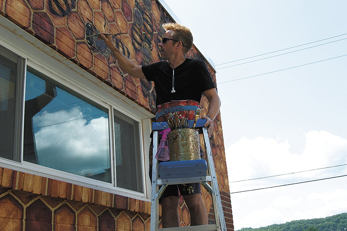 Matthew Willey is painting a bee hive on the side of the post office that he feels best represents the spirit of Narrowsburg.