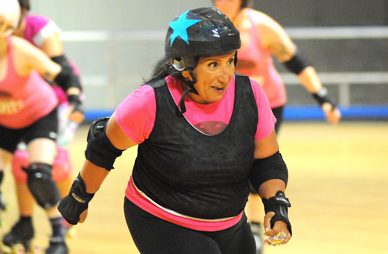 "A study in intensity. Sandra Oxford aka ""Sandstorm"" breezes down the roller derby rink in search of prey."