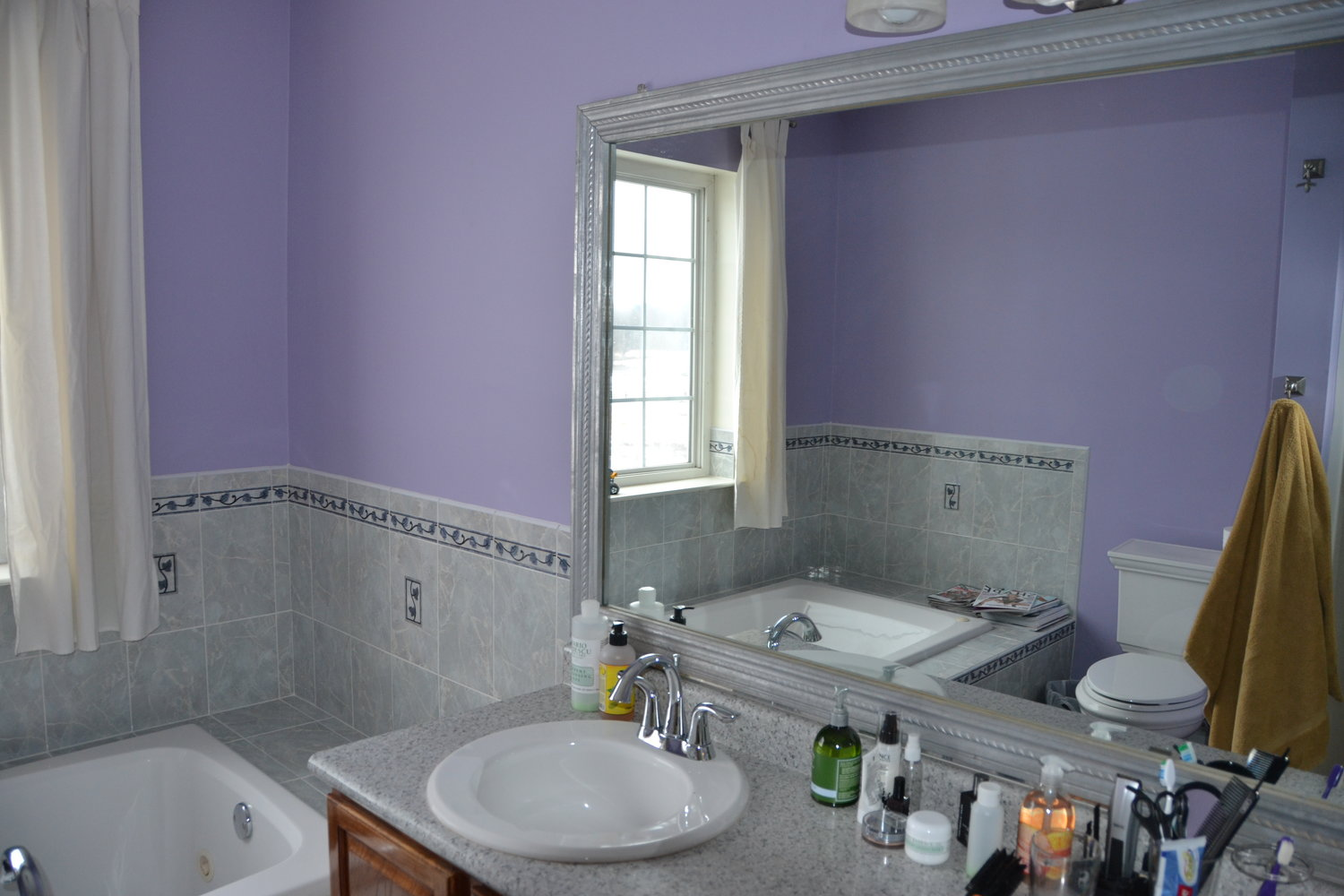 "You may love purple in the bathroom, but buyers don't. Here's the ""before"" of a bathroom Gray-Plaisted consulted on for the sellers."