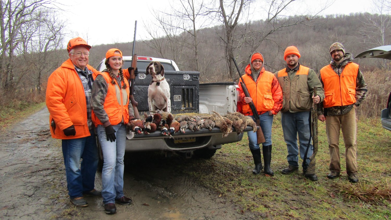 The family lines up to boast a tailgate full of pheasants and chukars harvested Thanksgiving morning.