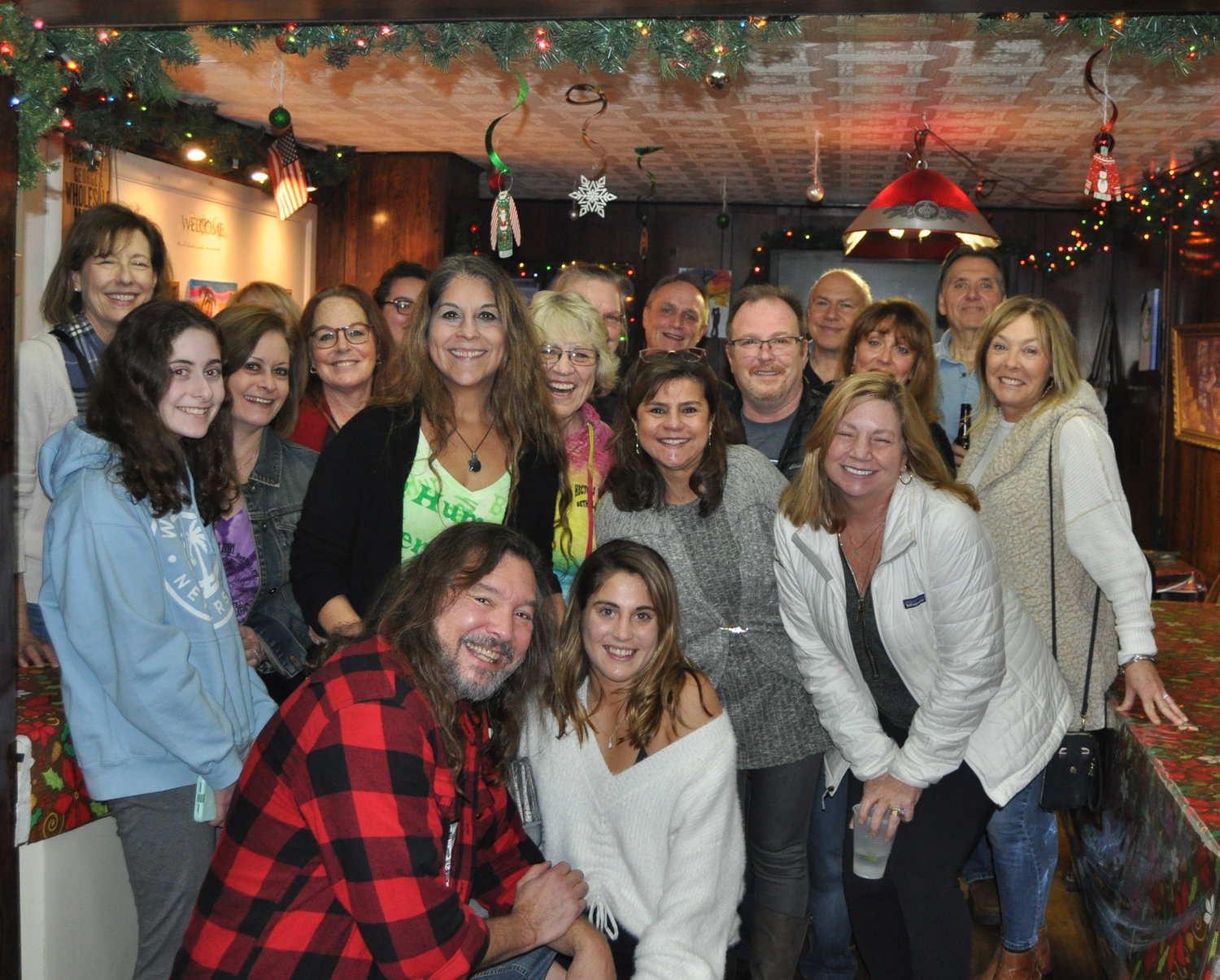 "Kim Simons, standing center, in the green shirt, is surrounded by friends and family at Hector's Inn in Bethel, NY to celebrate Simons' team Bah Hum Bakers and their $25,000 first prize win on the Food Network's ""Holiday Wars."""