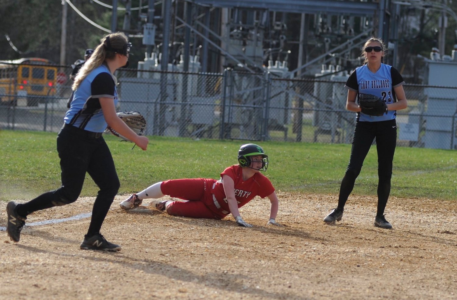 Double-teamed. Liberty's Katy Decker is safe at third, surrounded by Riley Ernst and Josephine Martinez of Sullivan West.