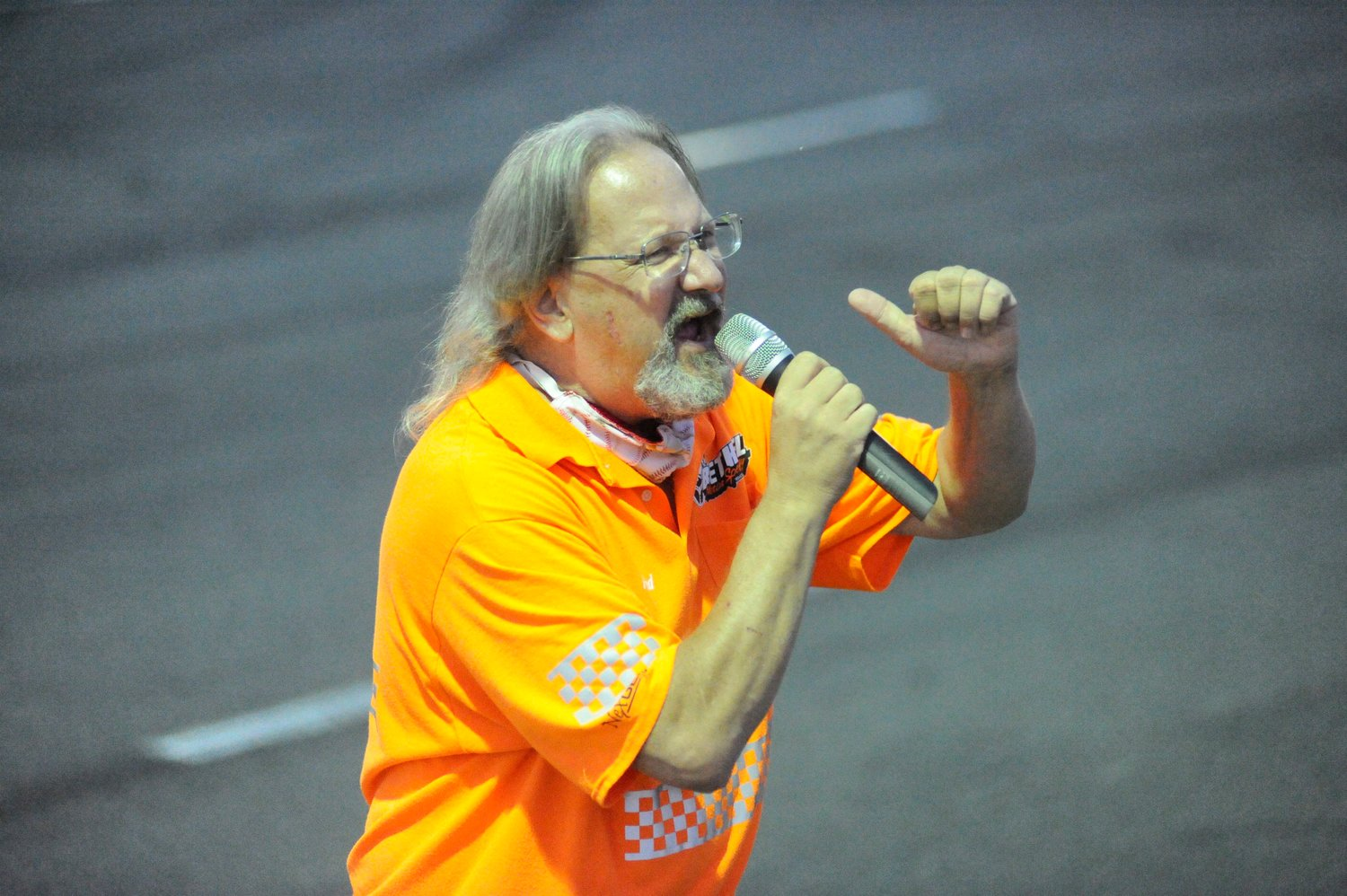 Let's hear it, folks! Fred Mulharin, the speedway's co-announcer, whips up the crowd during intermission.