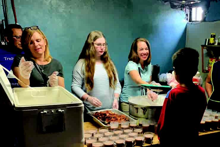 IMB missionary and translator Jennier Barger (left) serves breakfast at a migrant shelter alongside TAB digital editor Hannah Muñoz (center) andcustomer service representative Amy Hacker (right).