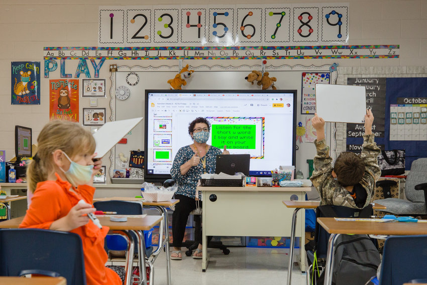Cathy Kersten, a first grade teacher at Manchester Elementary School, works with students in the classroom on a hybrid day in October 2020.