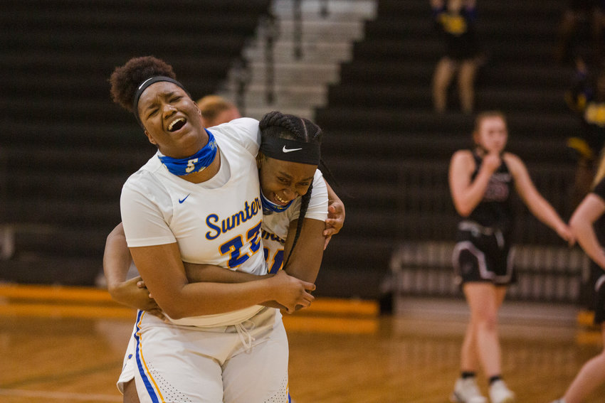 Sumter's Layken Cox (22) and Alicia Spann celebrate the Lady Gamecocks' 34-27 victory over Wando in the 5A lower state championship on Monday.