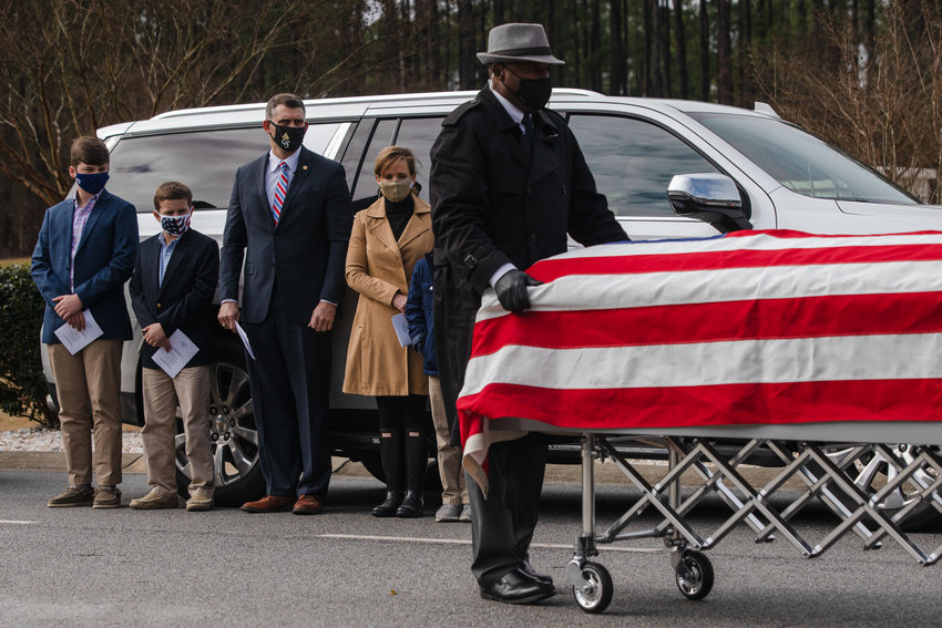 Sumter Mayor David Merchant and his family look on while the casket of Jerry Lynn White is moved before his funeral at Fort Jackson Cemetery on Wednesday.