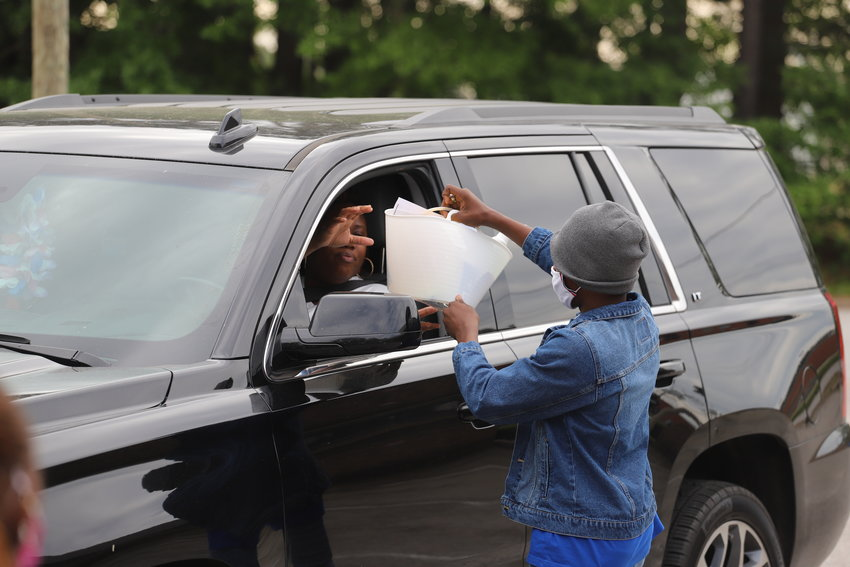 JaShawn Stukes, student body president at Ragin Preparatory Christian Academy, hands a cleaning supply basket to a resident in her vehicle. The school hosted a household supplies giveaway on Saturday.
