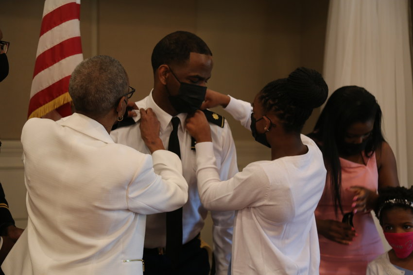 Maj. Glenn Canty's mother and oldest daughter pin him into a new rank during his promotion ceremony.