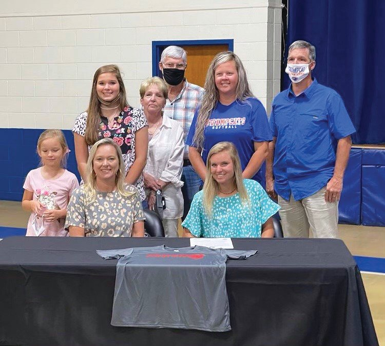 Laurence Manning's Madison Truett, seated right, is joined by family, friends and coaches as she signed her letter of intent to play softball at Newberry College on Wednesday.