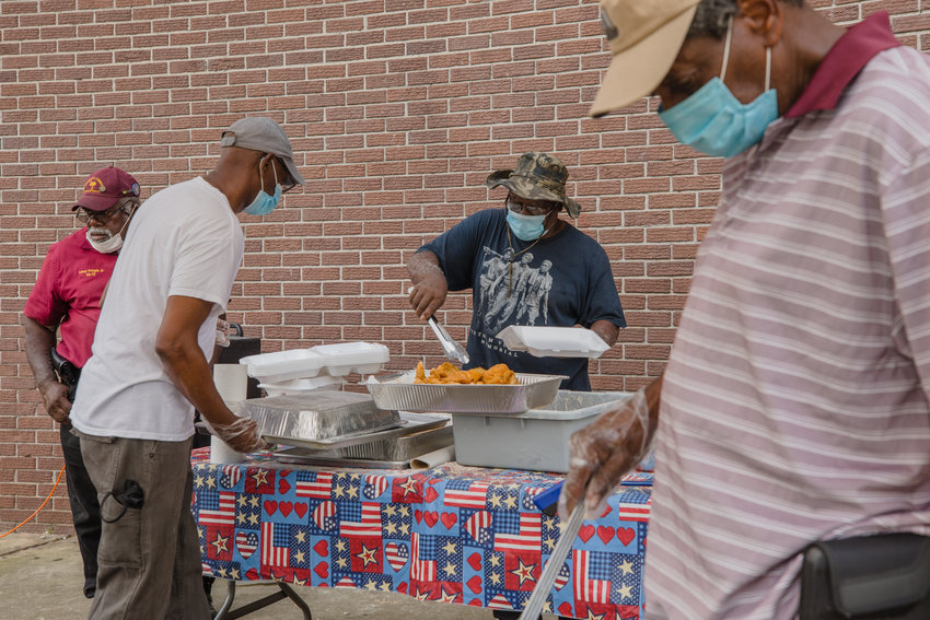 James Green boxes up fried fish with Perry Molten at the South Sumter Park Memorial Day fish fry. Due to the pandemic, the event was modified to a drive through in its 11th year.