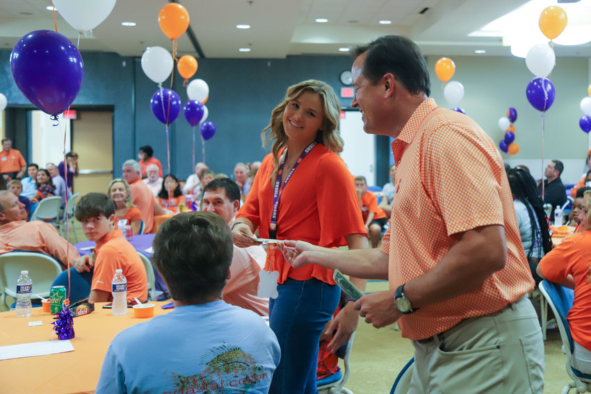 Hannah Merchant receives her Clemson-stamped $2 bill on Thursday at the Sumter Area Clemson Club's send-off event for the Class of 2025 and Class of 2024.
