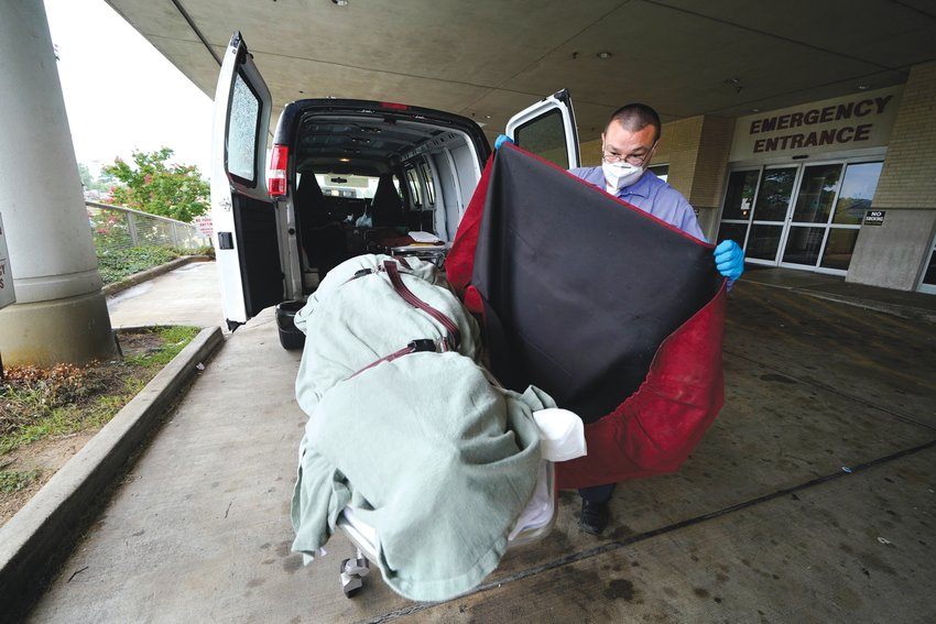 An employee of a local funeral home covers the body of a COVID-19 patient who died as he prepares to take it away from a loading dock at the Willis-Knighton Medical Center in Shreveport, Louisiana, on Aug. 18. COVID-19 deaths in the U.S. have climbed to an average of more than 1,900 a day for the first time since early March.