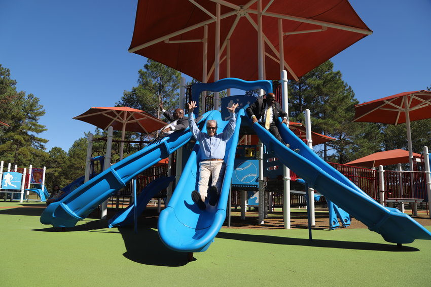 From left, state Rep. David Weeks, D-Sumter, Sumter County Councilman Charles Edens and Sumter City Councilman James Blassingame test out the Patriot Park playground equipment on Tuesday.