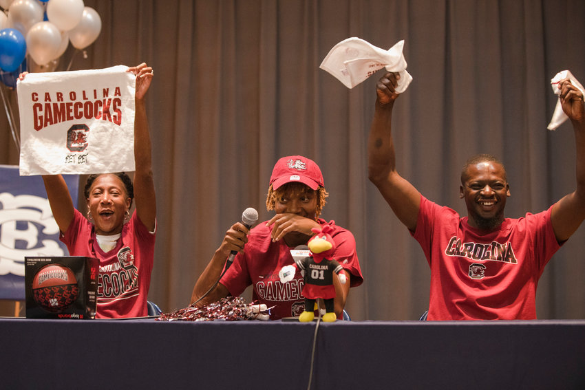 Talaysia Cooper on stage with her parents Letessa Porter and Travis Cooper after announcing she signed to play basketball at the University of South Carolina on Saturday in the East Clarendon gym.