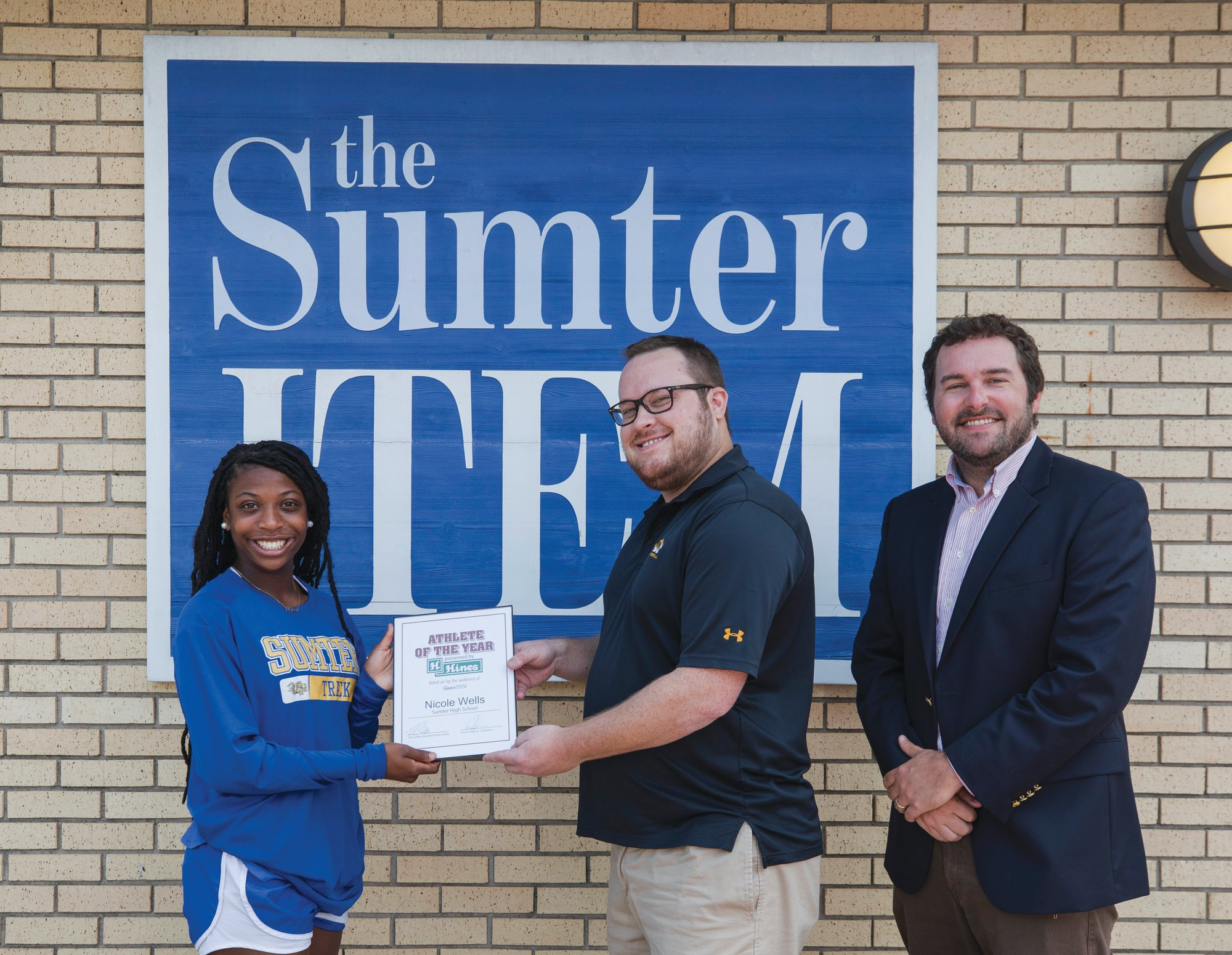 Sumter High track star Nicole Wells, left, is presented with the Hines Furniture Athlete of the Year by The Item's assistant sports editor, Tim Leible, center, and publisher Vince Johnson at the Item office on Tuesday.
