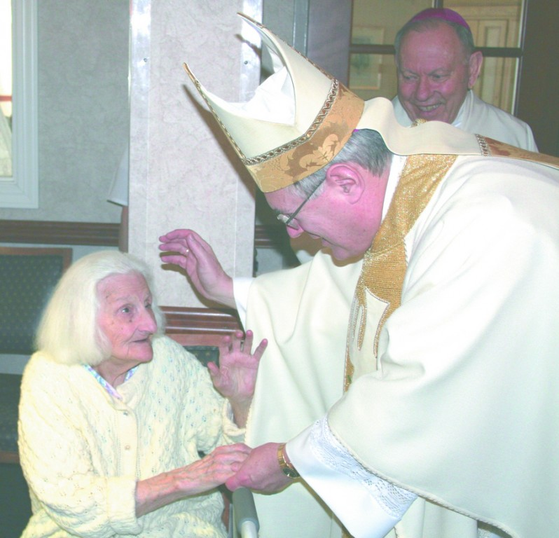 Bishop Thomas J. Tobin blesses 95-year-old nursing home resident Ida Amore, left, during a visit to the St. Antoine Residence in North Smithfield in January.