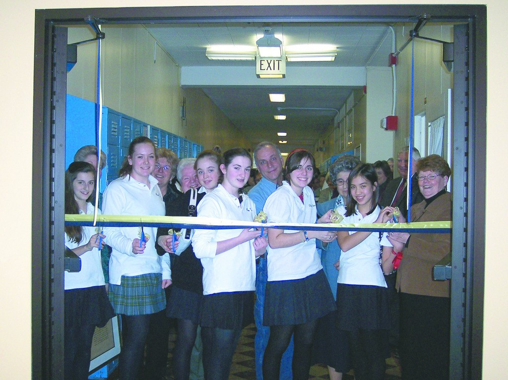 RIBBON CUTTING: Students and faculty cut the ribbon opening the new Gribbin Library at St. Mary Academy-Bay View. The library is named in honor of principal Colleen Gribbin, far right.
