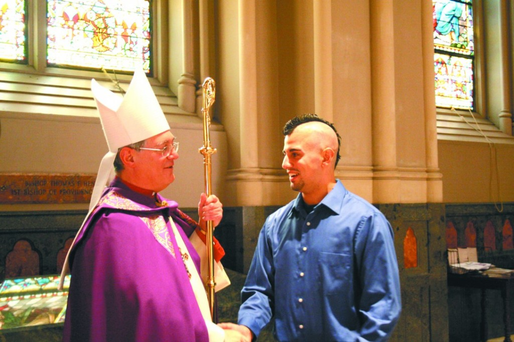 URI student Jason Coppa of Christ the King Parish in Kingston was among several hundred participating in the Rite of Election last Sunday at the Cathedral of SS. Peter and Paul in Providence, here warmly shaking hands with the Bishop.