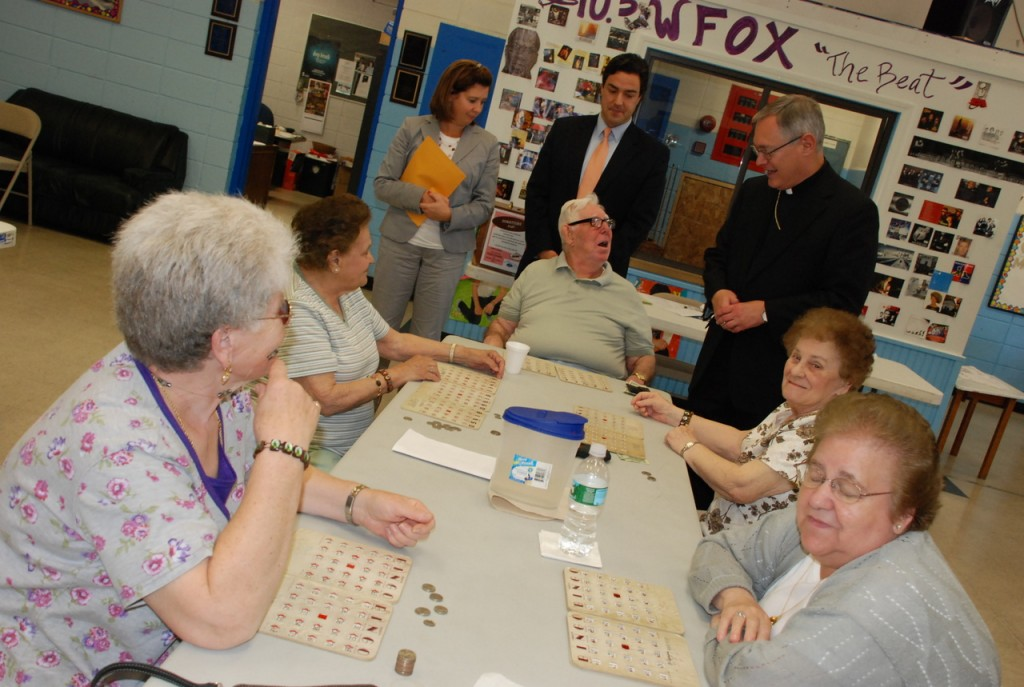"""A GOODWILL TOUR: Nicole R. Dufresne, upper left, chief operating officer of the Boys and Girls Club of Providence, David Bodah, senior director of development and marketing for the club, and Bishop Thomas Tobin greet senior citizens playing bingo at the Fox Point Boys and Girls Club on Wednesday, June 17. Bishop Tobin presented the club with a $5,000 check for its """"Keep the Lights On"""" campaign."""